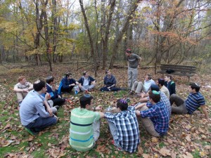 A group of jewish men sitting on the ground in the woods