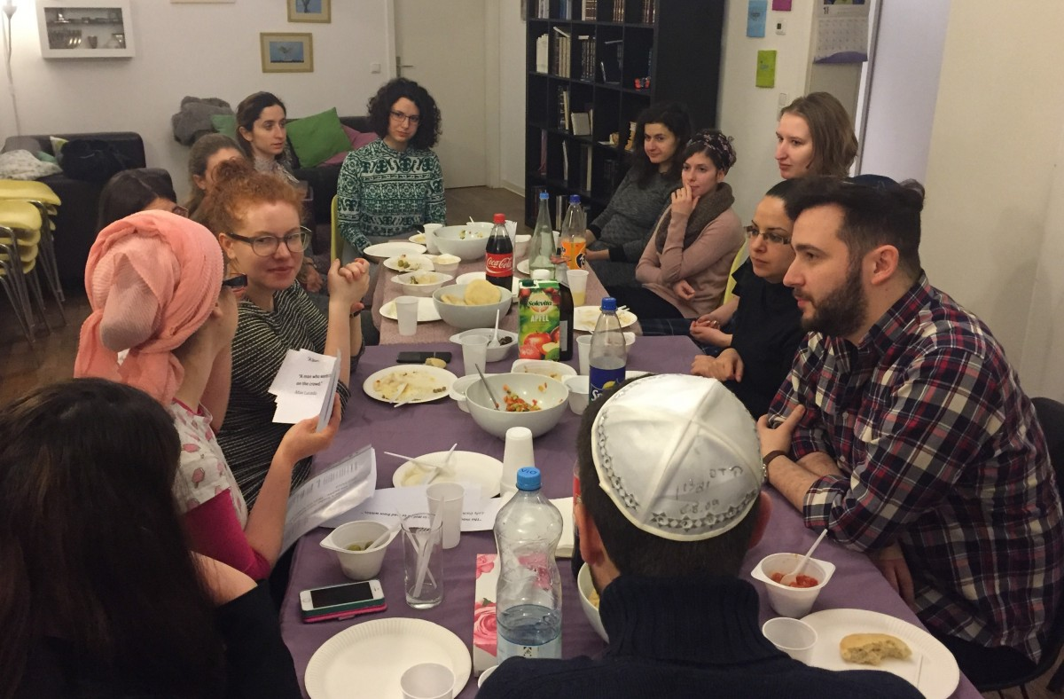 Jewish women and men around a table with food